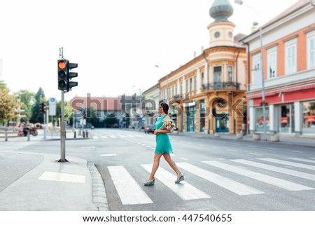 Stylish woman walking on a crosswalk in the city with bouquet of flowers - stock photo