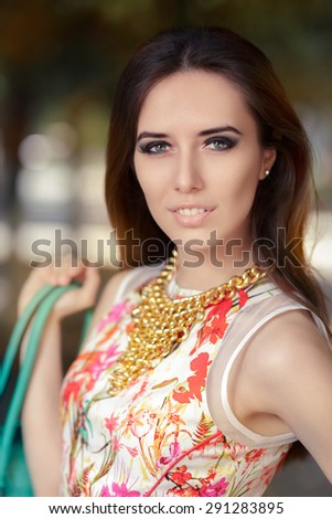 Stylish Woman Wearing Floral Dress, Necklace and Purse - Portrait of a trendy girl with handbag and gold chain necklace   - stock photo