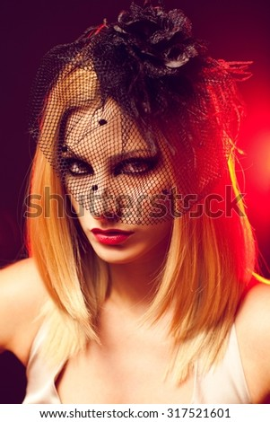 Stylish woman with a fascinator posing - backlit by red light.