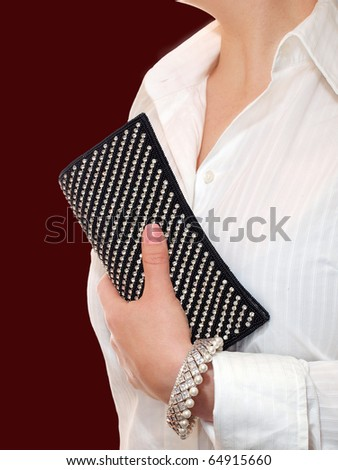 Stylish woman with evening clutch bag and silver bracelet