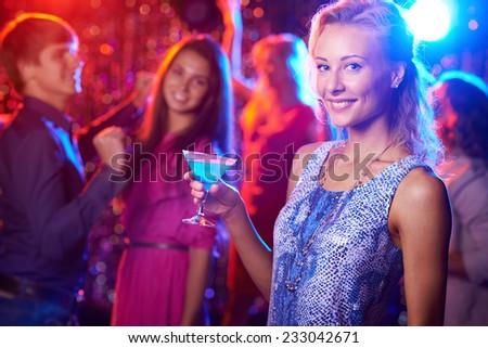 Stylish woman with martini glass posing at nightclub - stock photo