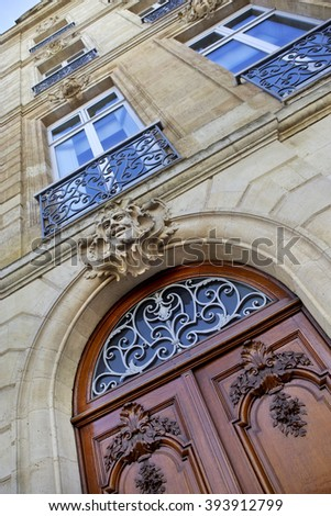 Stylish wooden door and stone facade in Bordeaux, France - stock photo