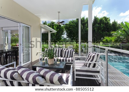 Stylish wooden outdoor deck overlooking a golf course and a swimming pool - stock photo
