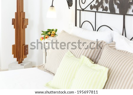 Stylish wrought iron double bed with striped pillows and bedroom decor with a modern wooden sculpture on the wall, close up detail - stock photo