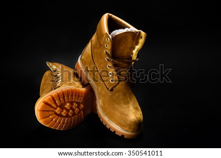 stylish yellow nubuck mens boots on black background, advertising concept - stock photo