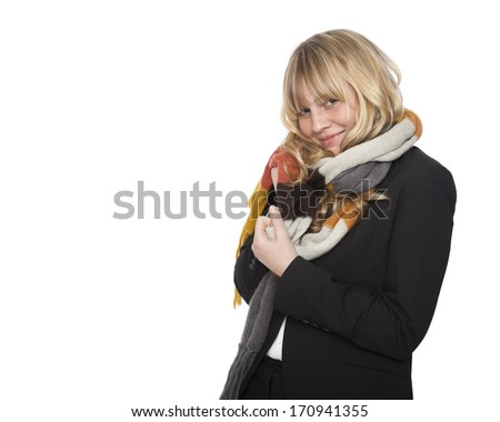 Stylish young blond woman in a winter scarf standing sideways smiling teasingly at the camera, isolated on white with copyspace - stock photo