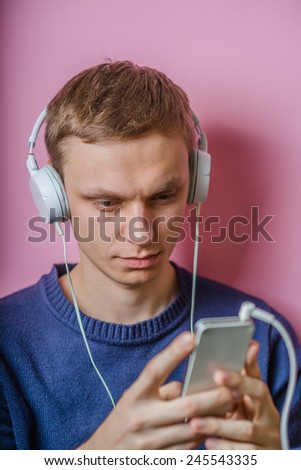 stylish young blonde hipster man listening to music
