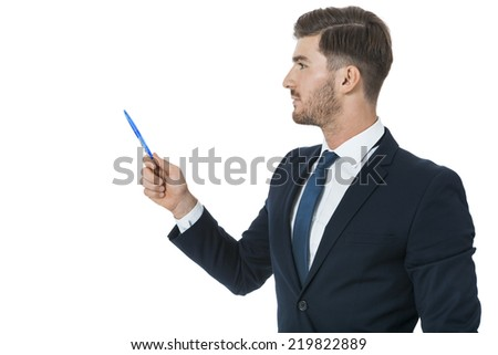 Stylish young businessman doing a presentation, making a selection or showing something pointing to the left of the frame with a pen in his hand as he stands sideways to the camera, isolated on white - stock photo