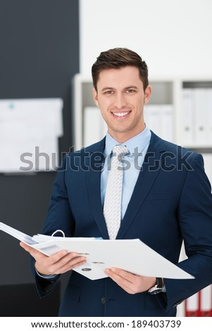 Stylish young businessman standing holding a large file in his hands as he smiles at the camera - stock photo