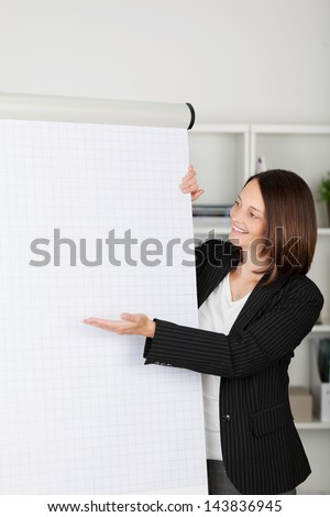 Stylish young businesswoman gesturing towards a blank flipchart with a smile during a presentation - stock photo