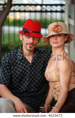 Stylish young couple in beautiful designer hats. - stock photo