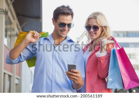 Stylish young couple looking at smartphone holding shopping bags on a sunny day in the city - stock photo
