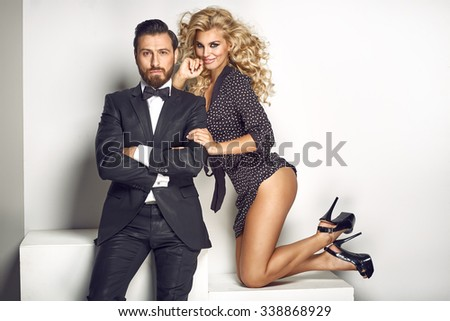 Stylish young couple posing close together and smiling - stock photo