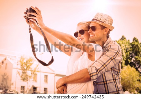 Stylish young couple taking a selfie on a sunny day in the city - stock photo