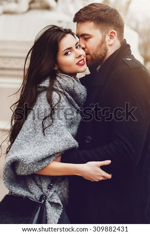 Stylish young couple walking on european autumn streets , have fun and hugging. Wearing trendy season outfit. Creamy  warm colors.