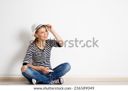 Stylish young female having fun and relaxing in her apartment. Cheerful Caucasian woman sitting at empty wall with her smart phone, listening song in headset. - stock photo