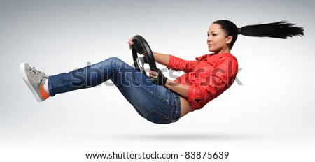 Stylish young girl driver in a coral color leather jacket with a steering wheel, concept of motion