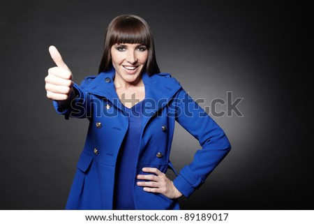 Stylish young girl in blue coat holding her thumbs up