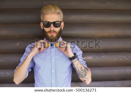 Stylish young hipster guy showing off with cool hand gestures.