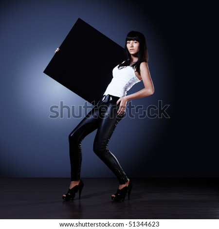 Stylish young lady holding blank black board