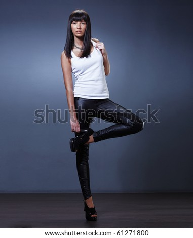 Stylish young lady standing holding her leg