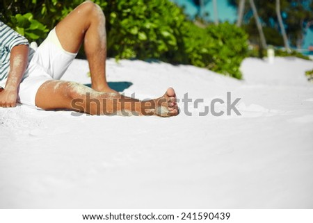 Stylish young male model man body lying on beach sand  wearing hipster cloth enjoying summer travel holiday near ocean in - stock photo