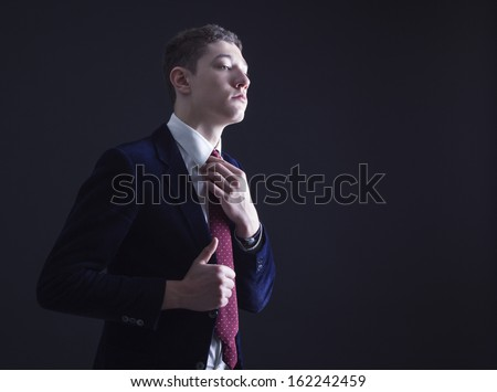Stylish young man in a blue suit and red tie. - stock photo