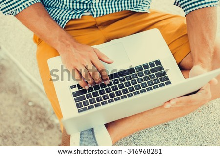 stylish young man in a shirt and shorts and sneakers working on laptop while sitting on the beach on the pier, sending mail, mounts, video editing and photography - stock photo