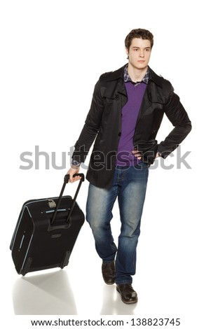 Stylish young man in jeans and jacket walking with travel suitcase, in full length, over white background - stock photo