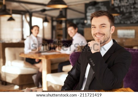 Stylish young man sitting in restaurant. closeup of handsome man drinking glass of red wine and friends on background - stock photo