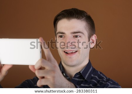 Stylish young man taking a selfie with his white smart phone on a light brown background - stock photo
