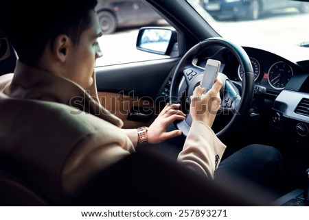Stylish young man using mobile phone in the car. Soft focus on the phone and hands - stock photo