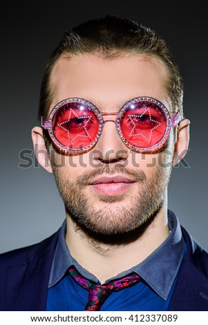 Stylish young man wearing party sunglasses smiling at camera. Fashion studio portrait.