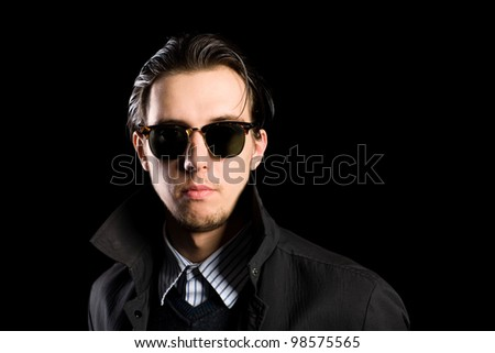 Stylish young man wearing sunglasses on a black background.