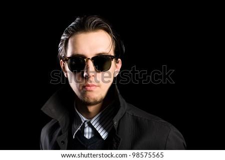 Stylish young man wearing sunglasses on a black background. - stock photo
