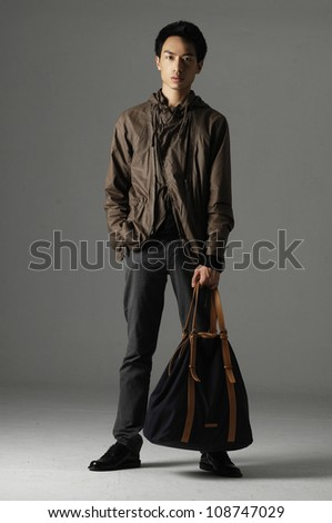 Stylish young man with bag standing on gray background