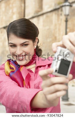 Stylish young tourist taking pictures of herself near a monument. - stock photo
