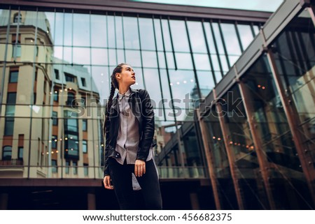 stylish young woman posing against a background of glass wall