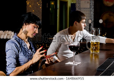 Stylish young woman sitting at the counter at the bar sending an sms message on her mobile phone, side view - stock photo