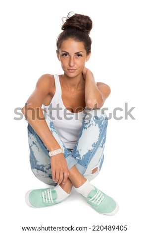 Stylish young woman sitting on the floor, isolated on white background. - stock photo