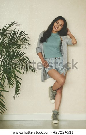 Stylish young woman standing at wall indoors - stock photo