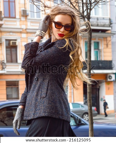 Stylish young woman walking on the street at nice sunny autumn day, wearing vintage coat and sunglasses. - stock photo