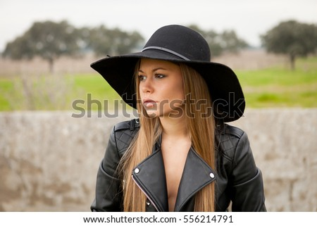 Stylish young woman with beautiful hat in the field