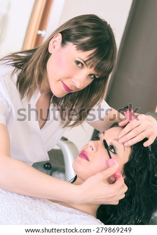 stylist applying makeup to a client in beauty salon - stock photo