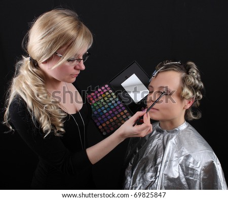 stylist beautician does her hair and makeup, preparing model shooting - stock photo