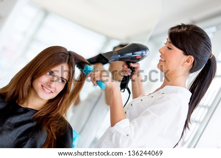 Stylist blow drying hair of a client at the beauty salon - stock photo
