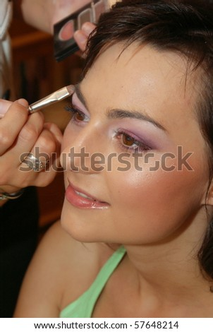 Stylist causes make up the beautiful model - stock photo