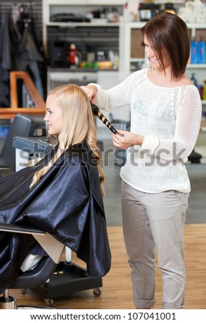 Stylist curling hair of a young blond customer - stock photo