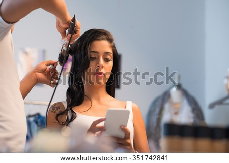 Stylist curling hair of glamorous young woman - stock photo