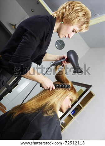 stylist drying woman hair in beauty salon. - stock photo